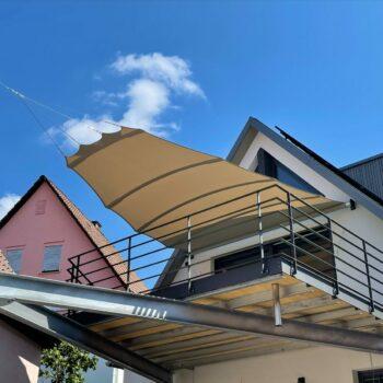 Graues Sonnensegel als Sonnenschutz auf dem Balkon.