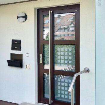 Aluminium-Haustüren mit drei unterteilten Glasflächen und kleinen Quadraten in Milchglas-Optik.