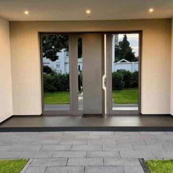 Haustüre aus Aluminium mit großen und verspiegelten Glasflächen.