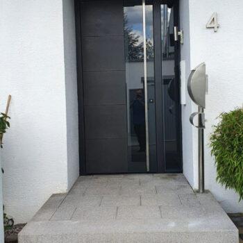 Haustüre aus Aluminium mit Glaseinsatz und Türgriff aus Metall.