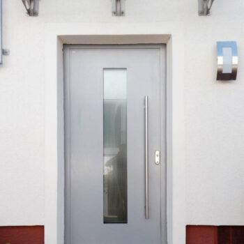 Haustüre aus Aluminium mit Glaseinsatz und langem Türgriff aus Edelstahl.