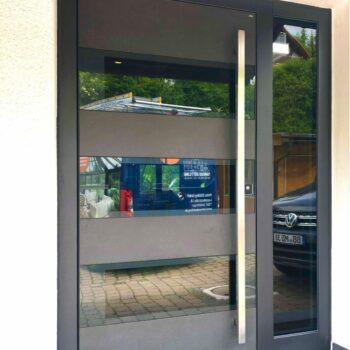 Moderne Aluminium-Haustür mit unterteilter Glasfläche.