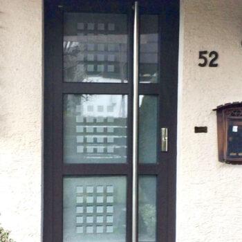 Aluminium-Haustür mit drei unterteilten Glasflächen und kleinen quadratischen Details in Milchglas-Optik.