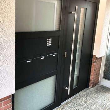 Aluminium-Haustür mit zwei großen Milchglasflächen und einem kleinen Glasstreifen als Detail.