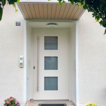 Aluminium-Haustür mit drei kleinen quadratischen und sichtgeschützten Glasflächen.