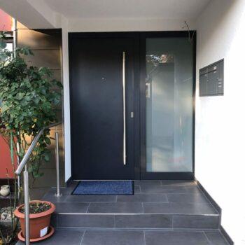 Schlichte Haustüre aus Aluminium mit einem Milchglaseinsatz auf der rechten Seite.