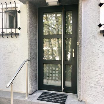 Aluminium-Haustür mit unterteilten Glasflächen und kleinen quadratischen Detail in Milchglas-Optik.