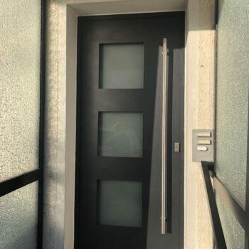 Aluminium-Haustür mit drei quadratischen Milchglasflächen.