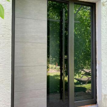 Einladende Haustüre aus Aluminium mit großer Glasfläche.