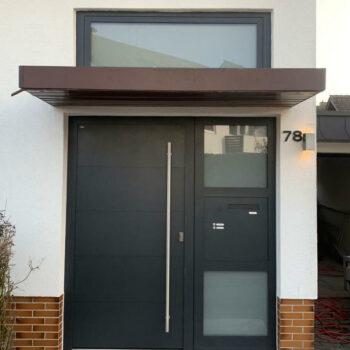 Aluminium-Haustür mit zwei kleinen Milchglasflächen und in schlichtem Design.