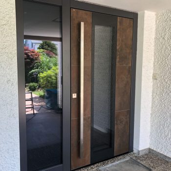 Moderne Haustüre aus Corten-Stahl mit zwei Glasflächen.