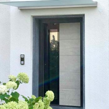 Moderne Haustür mit sandfarbenem Detail und Glasfläche.