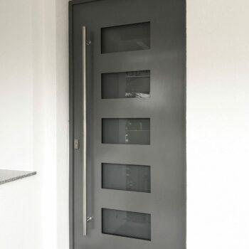 Aluminium-Haustür mit fünf kleinen Glasflächen mit Sichtschutz.