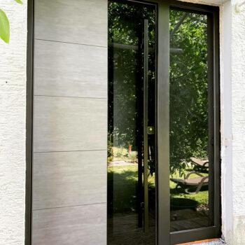 Haustüre aus Aluminium mit großer Glasfläche und silbernem Einsatz.