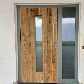 Haustüre aus Holz mit Glaseinsatz und Rahmen aus Aluminium.