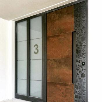 Moderne Haustür aus Corten-Stahl mit zwei großen Milchglasflächen.