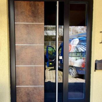 Moderne Haustür aus Corten-Stahl und mit zwei Glasflächen.