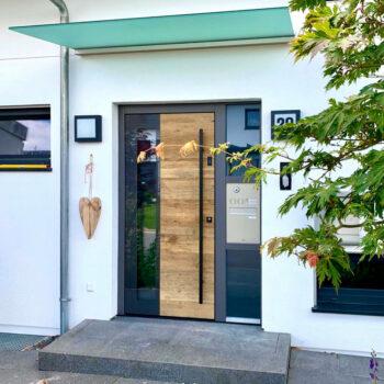 Moderne Haustüre aus Holz mit Aluminium-Rahmen und mit viel Glasfläche.