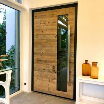 Haustüre aus Holz mit Aluminium-Rahmen, kleiner Glasfläche und einem Türgriff aus Metall.