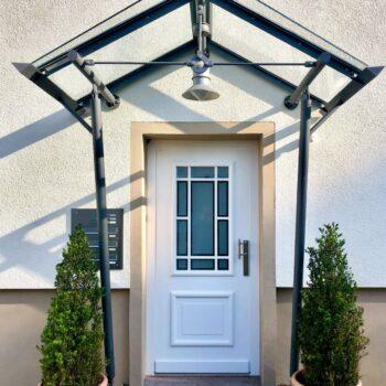 Weiße Holz-Haustür mit dünnen Sprossen und Glasfläche.