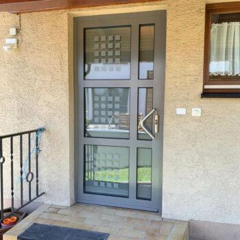 Aluminium-Haustür mit unterteilten Glasflächen und kleinen Quadraten in Milchglas-Optik.
