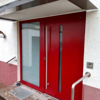 Rote Haustüre mit schmaler Glasfläche als Detail und Milchglasfläche