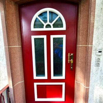 Rote Haustüre aus Holz mit kleinen Glasflächen und Details in Weiß.