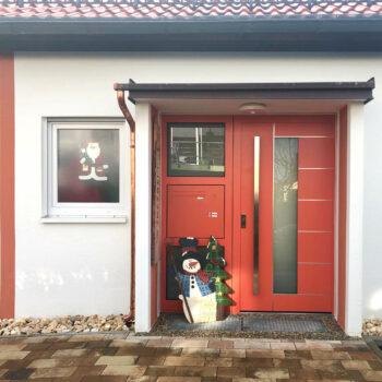 Aluminium-Haustür in rot mit zwei Glasflächen und silbernen Details.