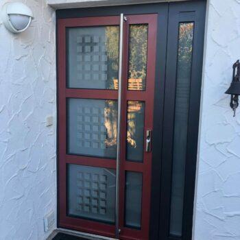 Aluminium-Haustür mit großen Glasflächen und kleinen quadratischen Details in Milchglas-Optik.