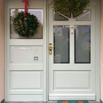 Haustür aus Holz in Weiß und mit sichtgeschützten Glasflächen.