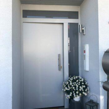 Silberne Aluminium-Haustür mit zwei schmalen Glasflächen.