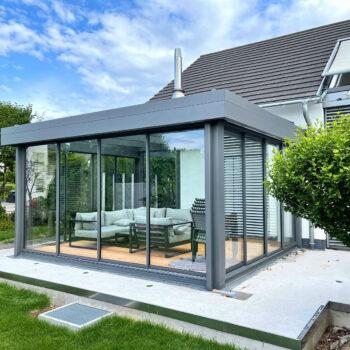 Moderner Wintergarten mit Glasdach und Glasschiebewänden.