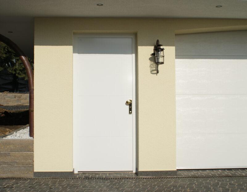 Schlichte Nebeneingangstür in Weiß.