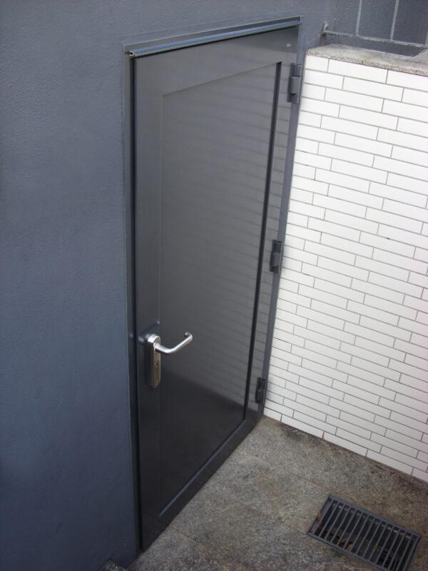 Schwarze Nebeneingangstür in modernem Design.