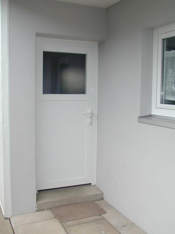 Weiße Nebeneingangstür mit blickdichtem Fensterglas.