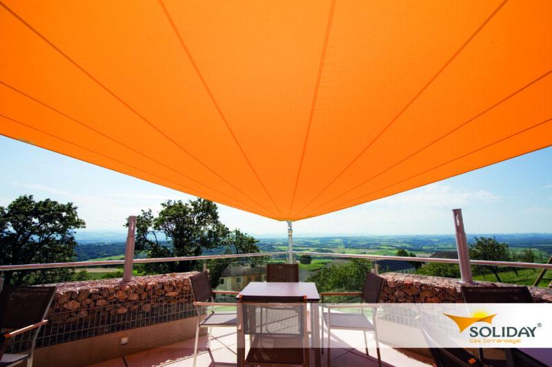 Orange farbiges Sonnensegel als Sonnenschutz für den Außenbereich der Gastronomie.