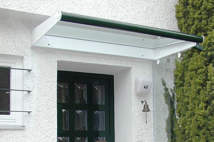 Modernes Vordach aus Glas mit grüner Kante und weißer Halterung.